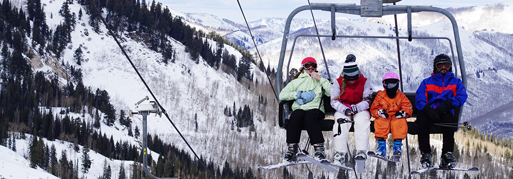 Four people sitting on a chair lift getting ready to ski down the mountain