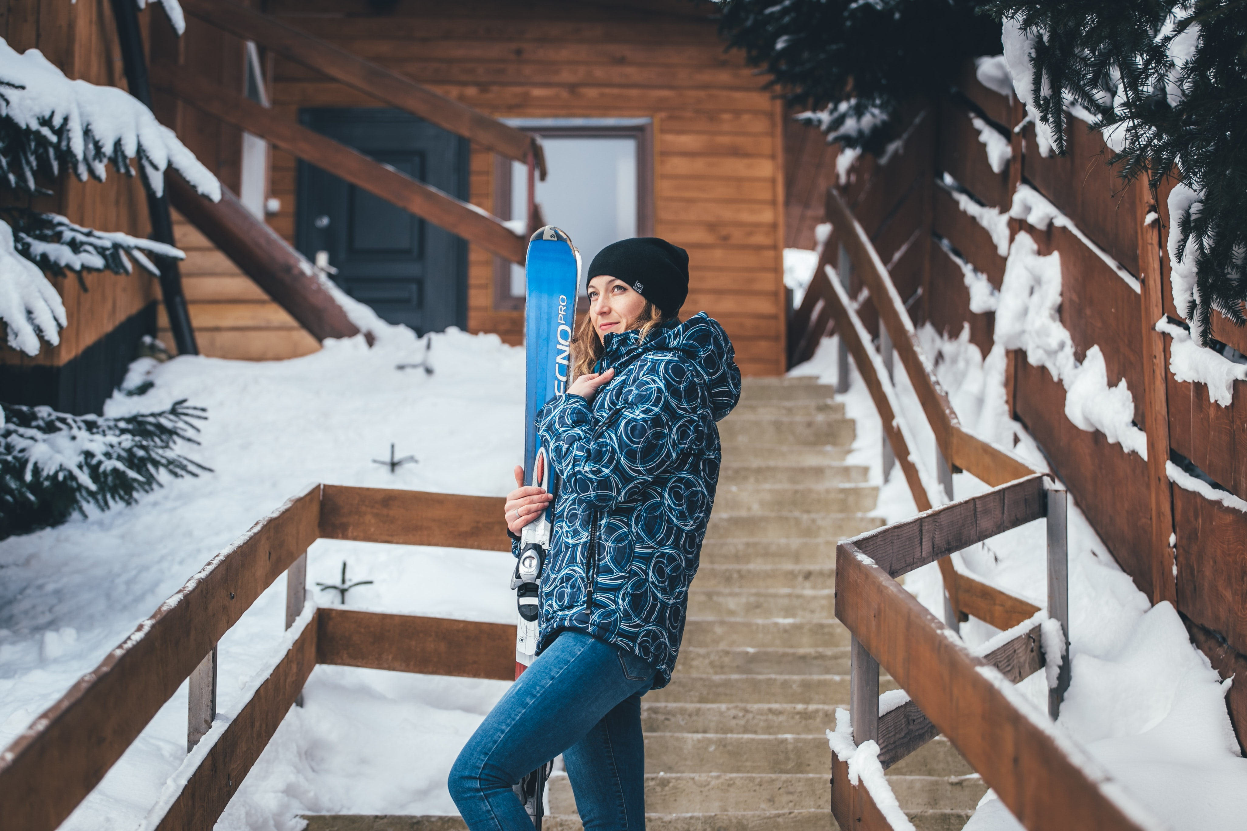 A girl skier standing by a log cabin