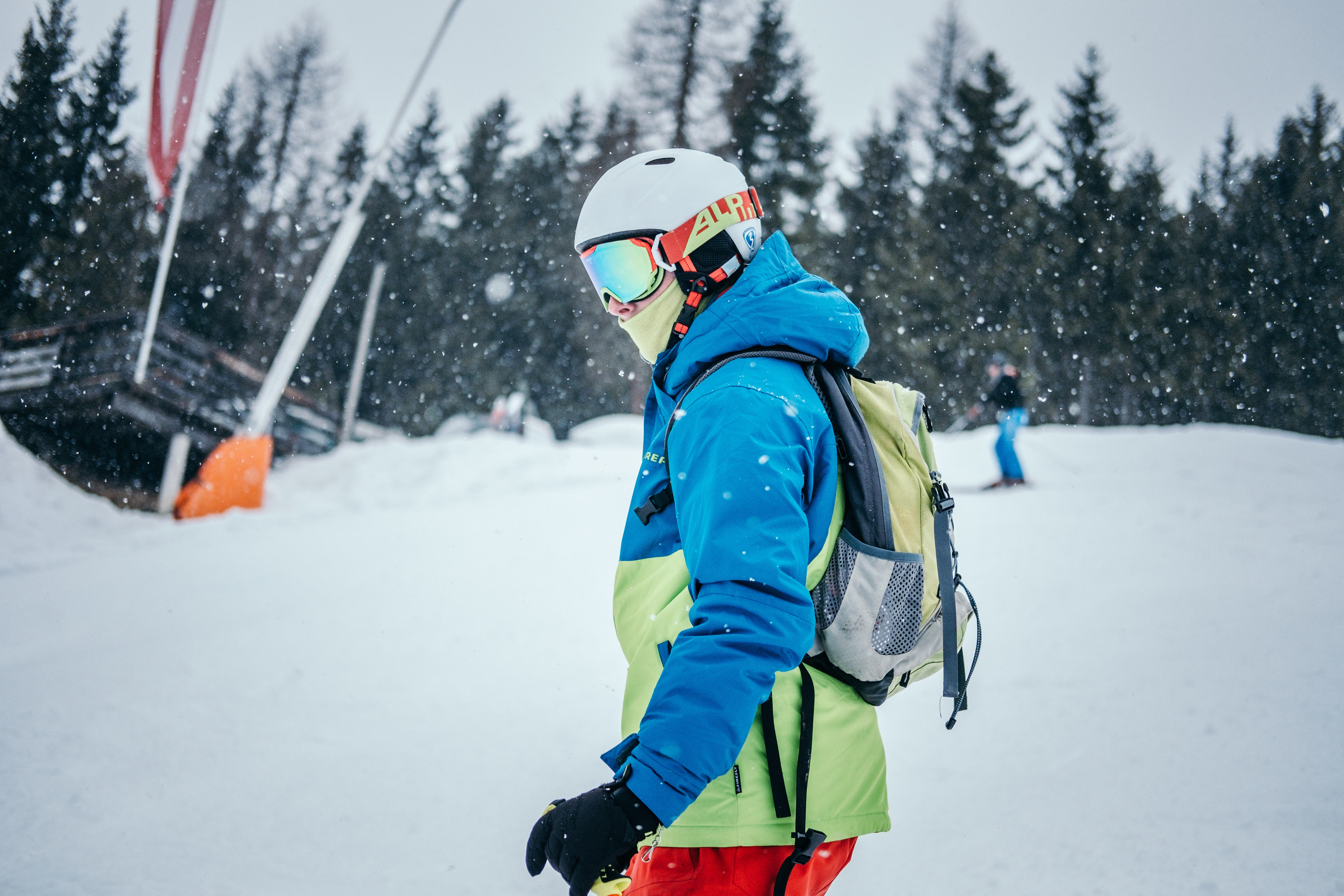 Man Skiing on the mountain with a blue jacket, neck gaiter, helmet, and goggles.